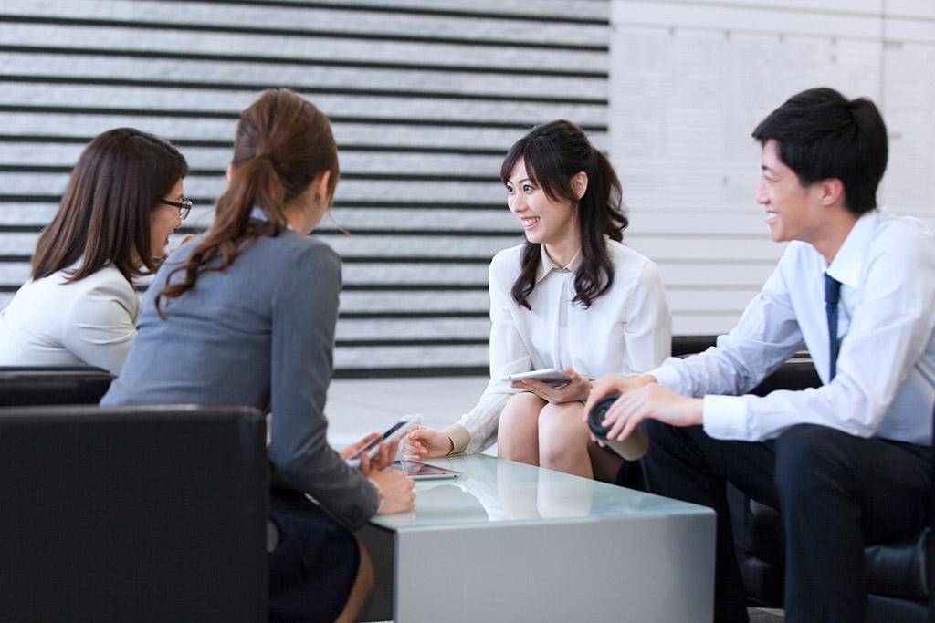 座って会話するビジネス男女4人