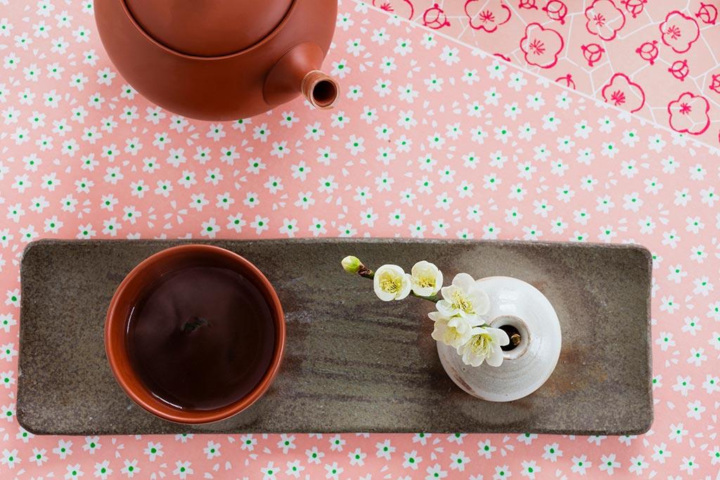 ほうじ茶の入った茶碗と一輪挿し