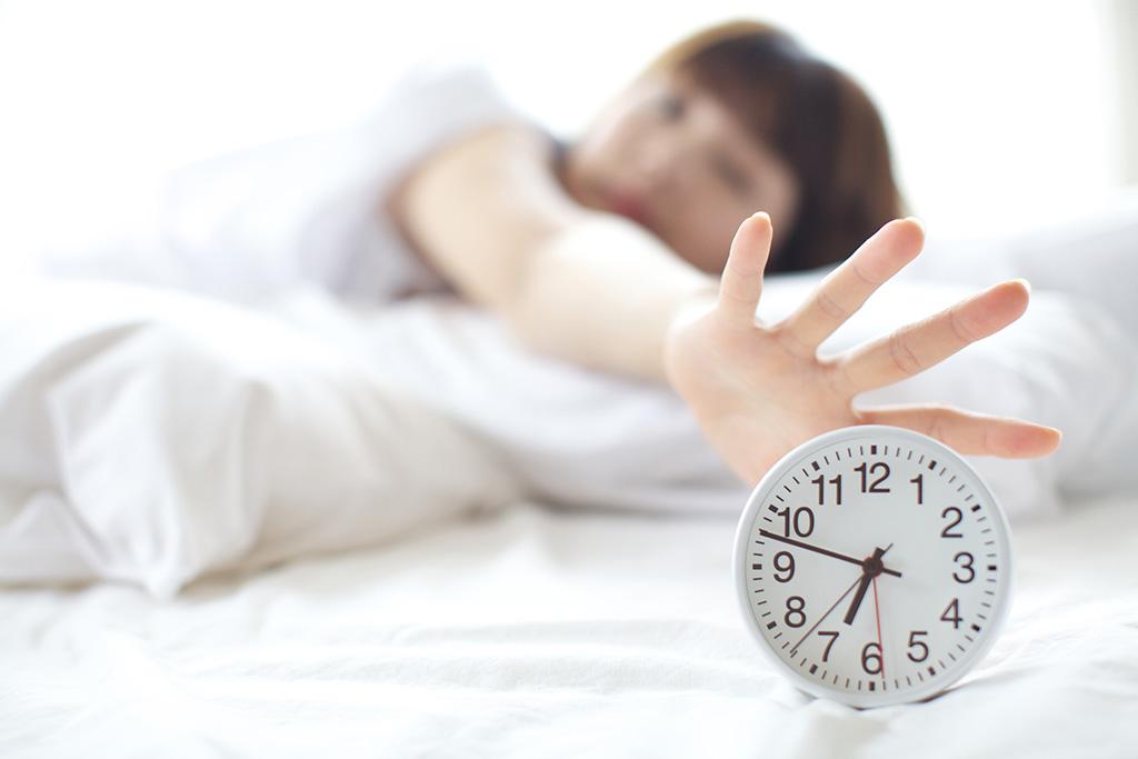 目覚まし時計を止めようとする女性