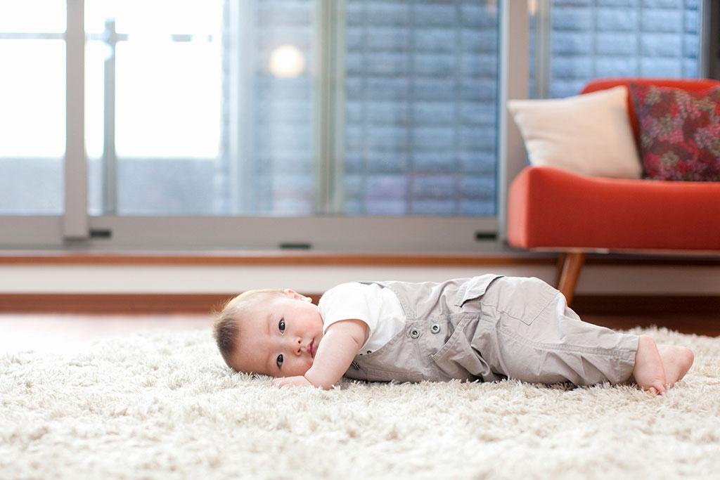 カーペットの上に寝そべる赤ちゃん