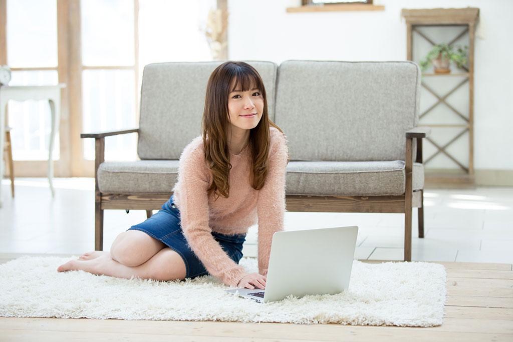 暖かそうなラグの上に座ってノートPCを操作する女性