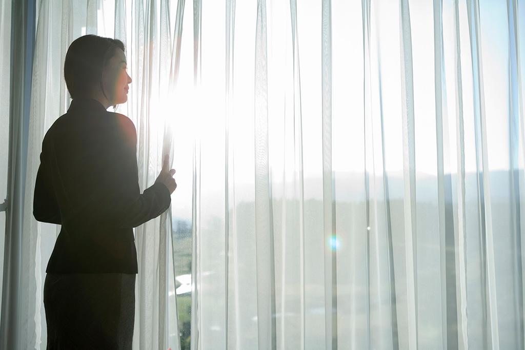 レースカーテンにして太陽の光を取り込む女性