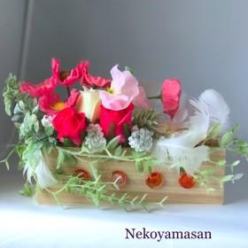 木箱のピンクのポピーと天使の羽のアレンジ