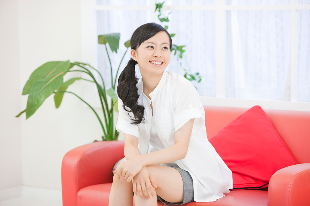 赤いソファに座る女性