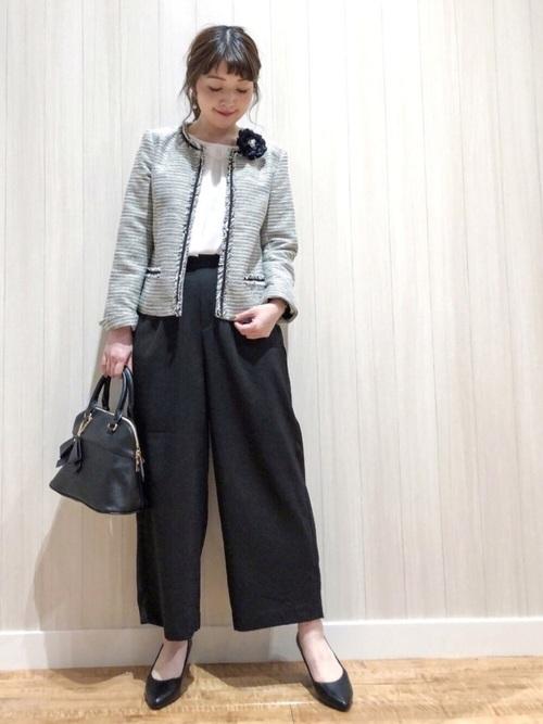 グレーのツイードジャケットと黒いパンツのコーデ