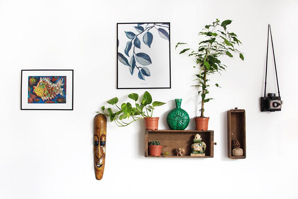 壁にかかる額縁と飾り棚、観葉植物