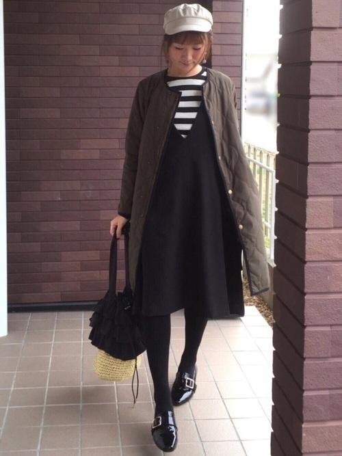 カーキのキルティングコートと黒いジャンパースカートのコーデ