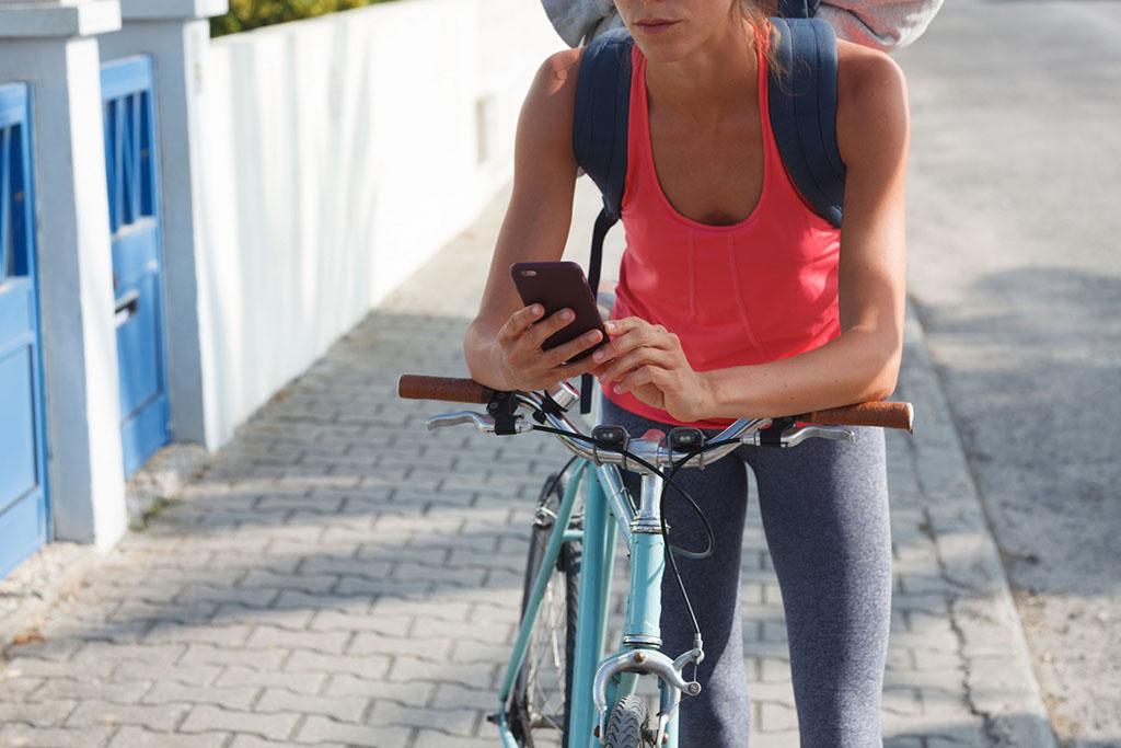 自転車からいったん降りてスマホを見る女性