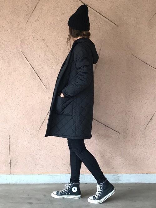 黒いキルティングコートとデニムパンツのコーデ