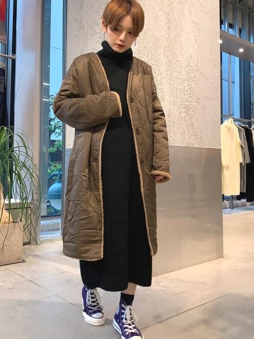 ベージュのキルティングコートと黒いワンピースのコーデ