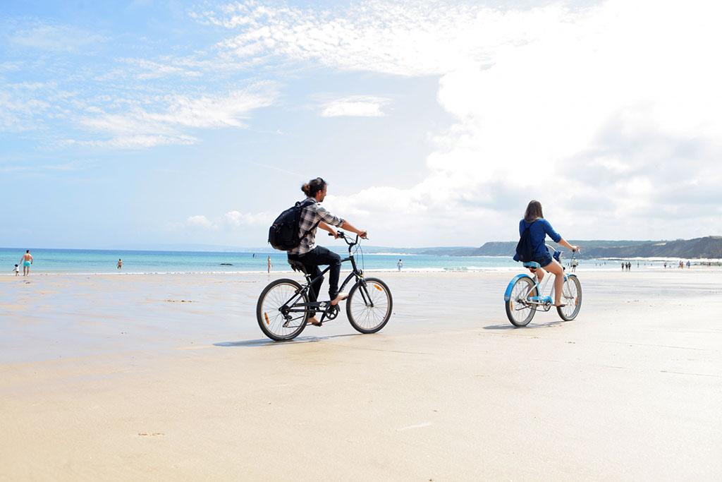 砂浜を自転車で走るカップル
