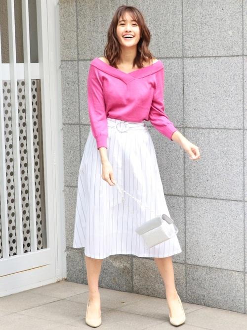ピンクのニットと白いフレアースカートのコーデ