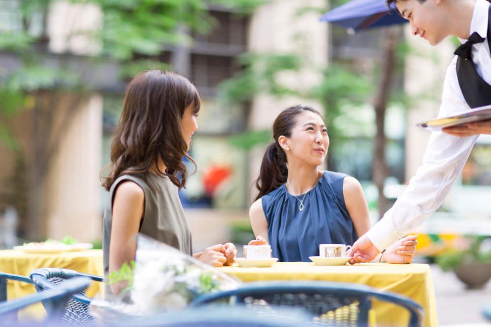 カフェのテラス席に座る2人の女性と店員