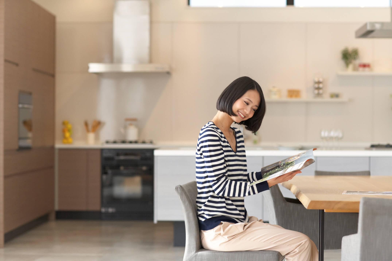 ダイニングテーブルで読書をする女性