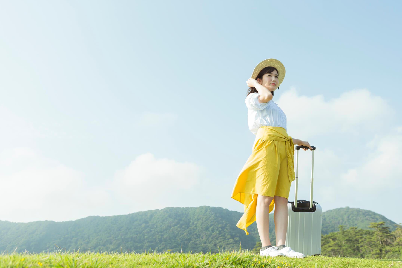トランクを持ち自然の中に立つ女性