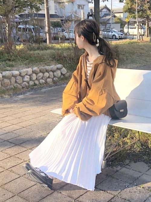 オレンジのナイロンジャケットと白いプリーツスカートのコーデ