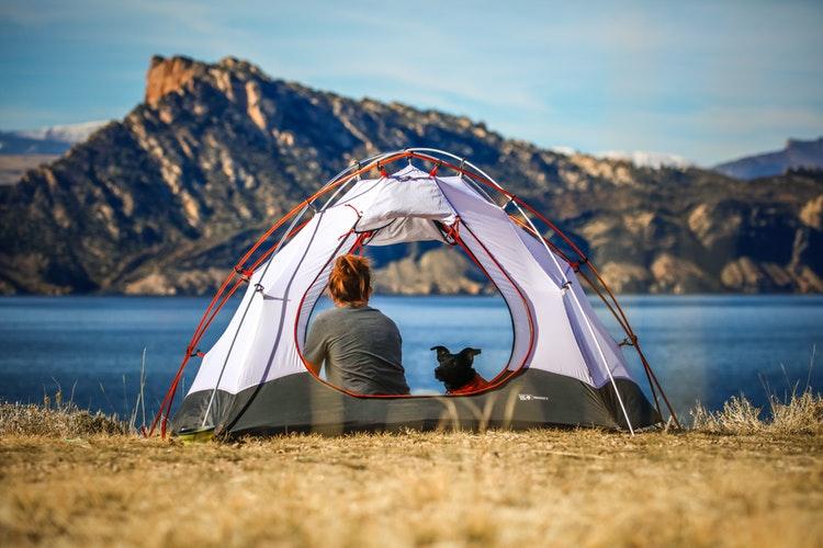 水辺にテントを設営してくつろぐ女性の後ろ姿