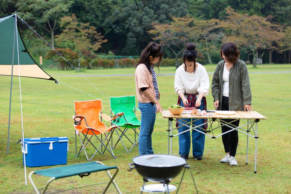 食事できるようにテーブルやいすを配置する女性