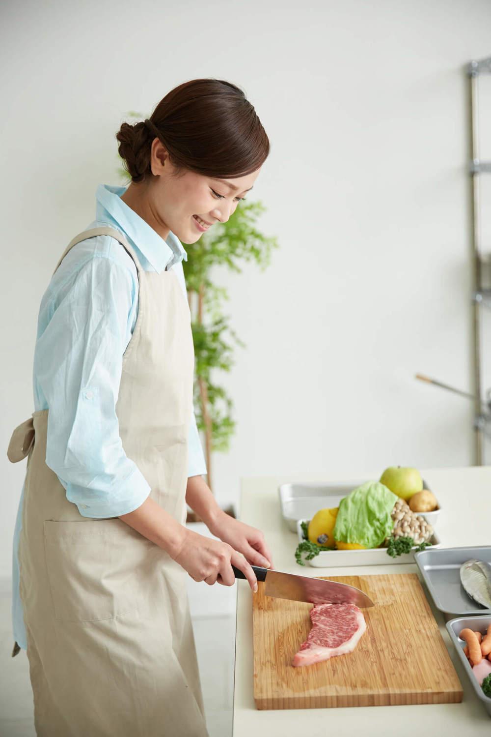 ステーキを調理する女性