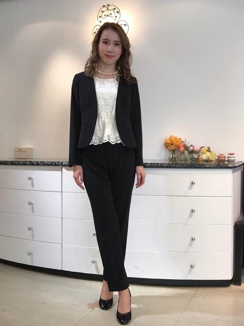 黒いパンツスーツと白いレース柄ブラウスのコーデ