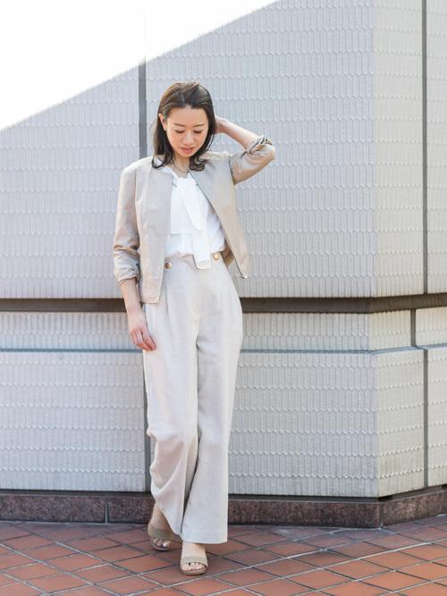 ベージュのパンツスーツと白いボウタイブラウスのコーデ