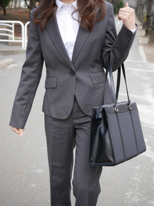 グレーのパンツスーツと白い襟つきシャツのコーデ