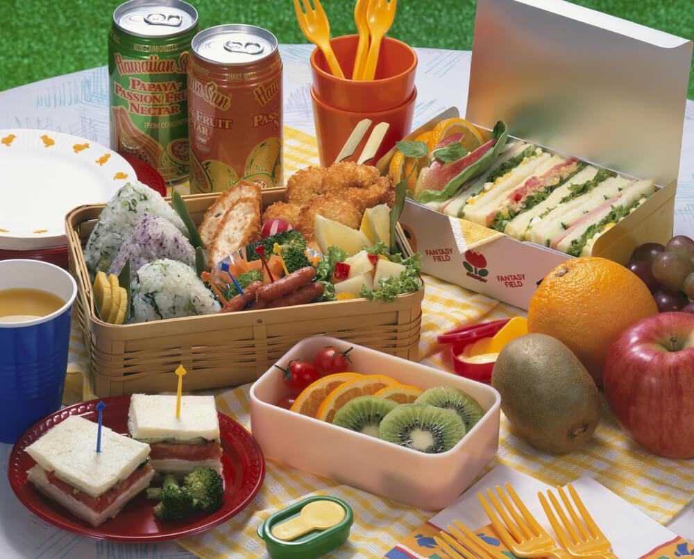 柳行李のおにぎり弁当とペーパーボックスに詰められたサンドイッチ
