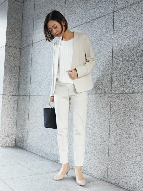 ベージュのパンツスーツと白いタックブラウスのコーデ