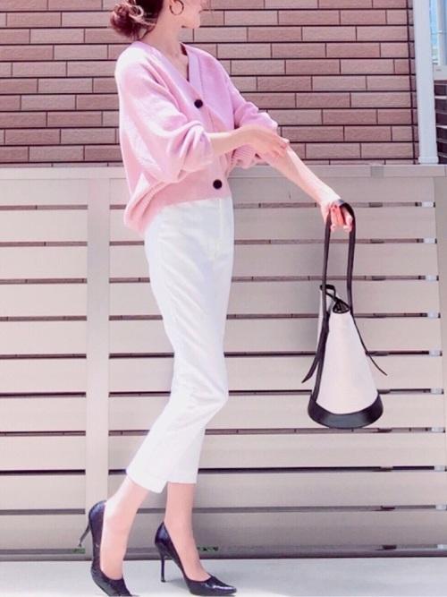 ピンクのカーディガンと白いパンツと黒いセットバックヒールのコーデ