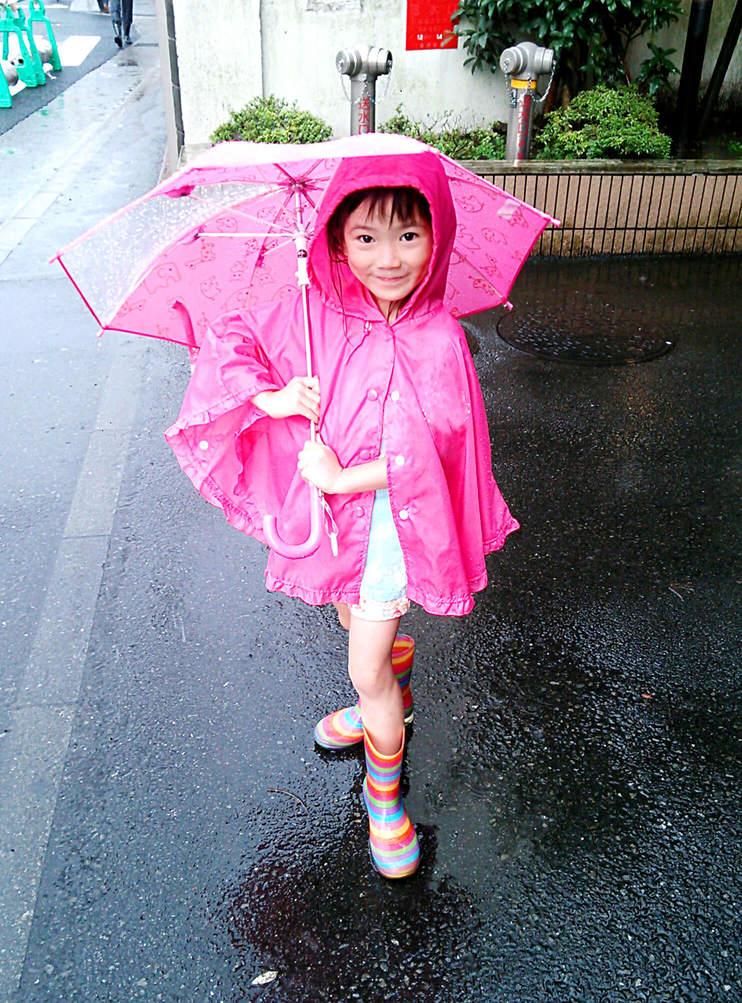 レインポンチョを着て傘をさす少女