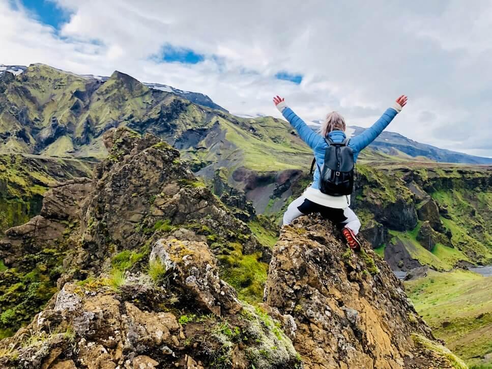 山の頂上でアウトドア用のウインドブレーカーを着ている人