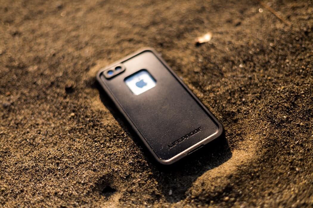 砂の上に置いている防水ケース入りのスマートフォン