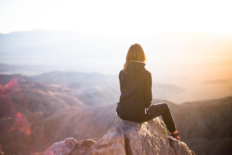 山の上で太陽の方向を向く女性