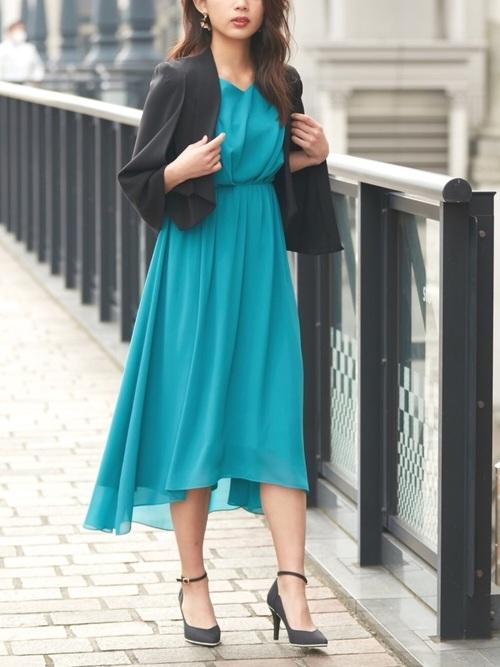 黒のテーラードジャケットとグリーンのドレスのコーデ