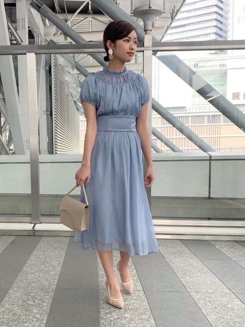 ブルーのドレスとベージュのハンドバッグのコーデ