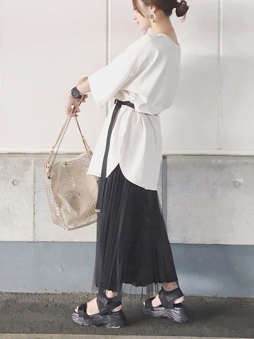 白いオーバーサイズTシャツと黒いプリーツスカートをベルトでウエストマークしたコーデ