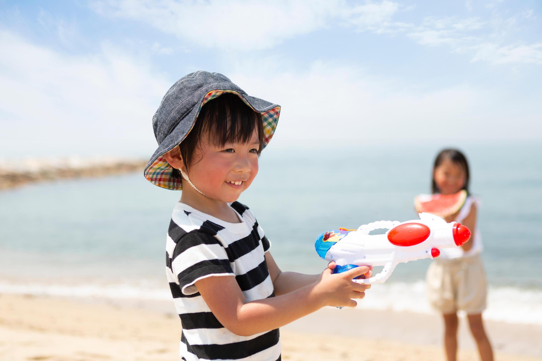 砂浜で水鉄砲を構える男の子