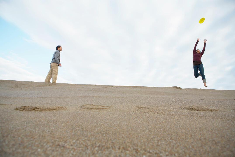 砂浜でフリスビーを投げて遊ぶ子どもたち