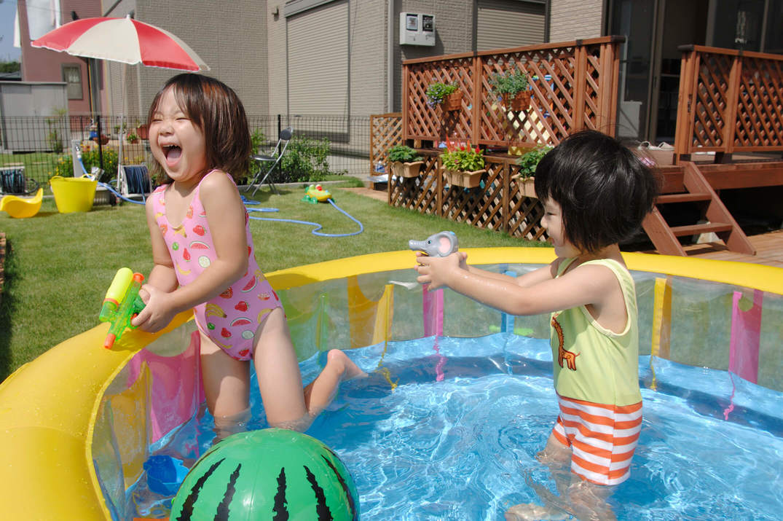 庭のプールで水鉄砲を使う女の子たち