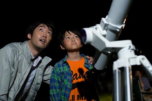天体望遠鏡と空を見上げる親子