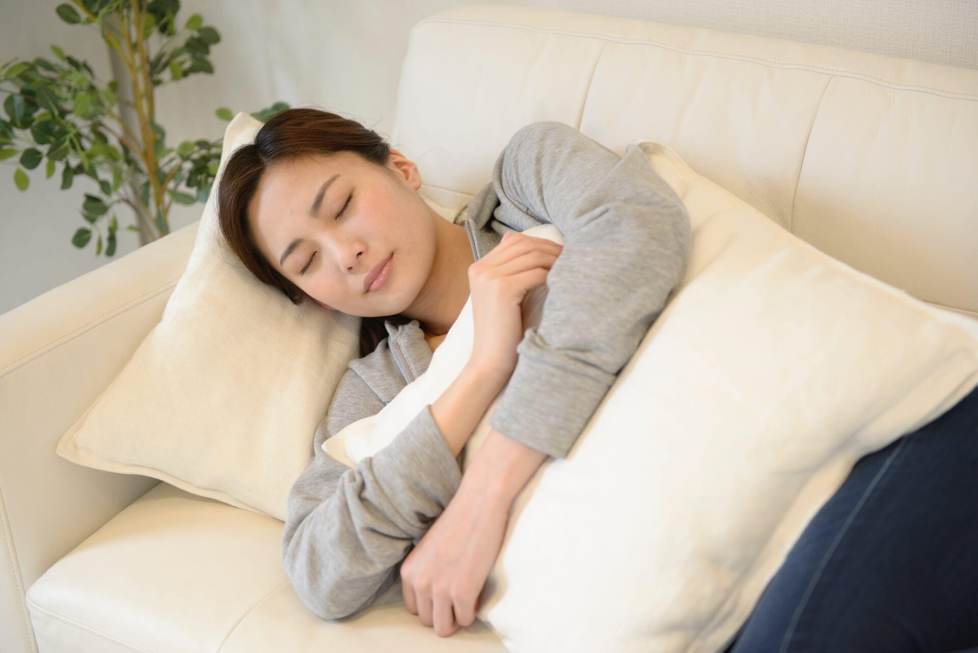 クッションを抱いてソファで眠る女性