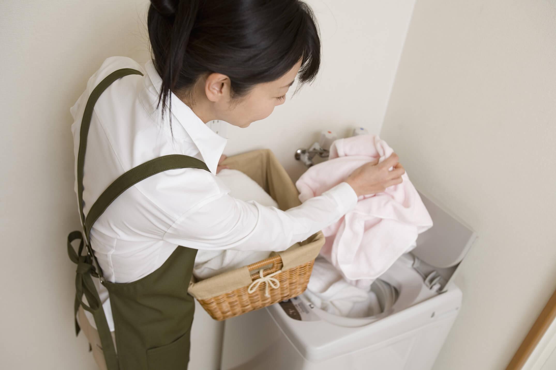 たくさんの洗濯物を洗濯機に入れる女性