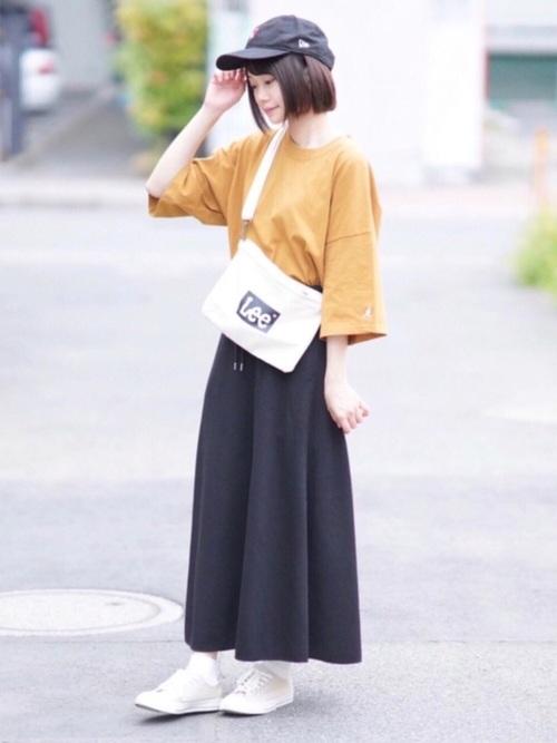 マスタード色のTシャツと黒いロングスカートのコーデ