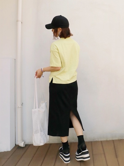 イエローのTシャツと黒いタイトスカートのコーデ