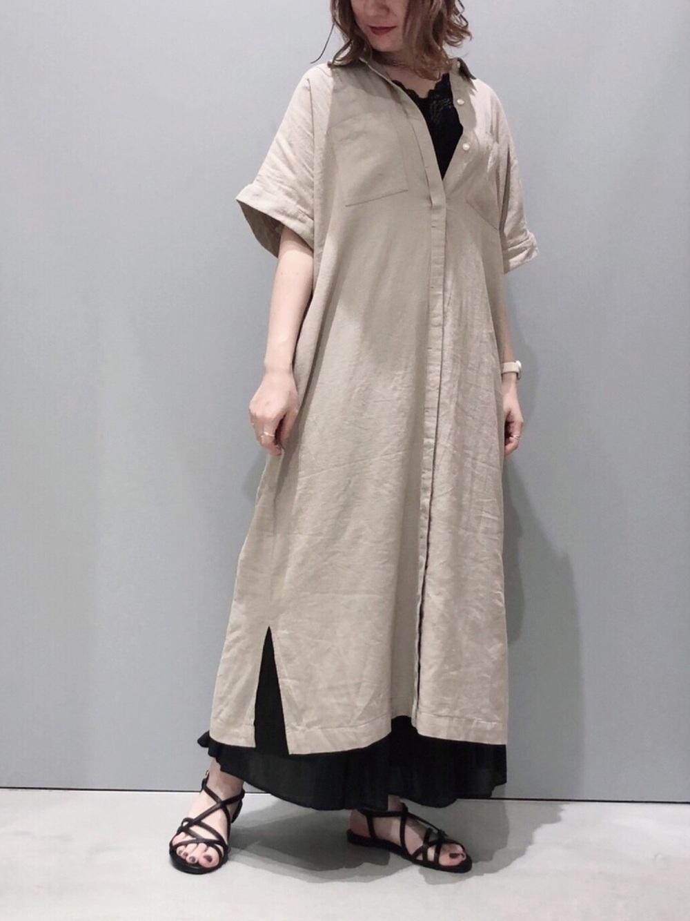 ベージュのシャツワンピースと黒のスカート