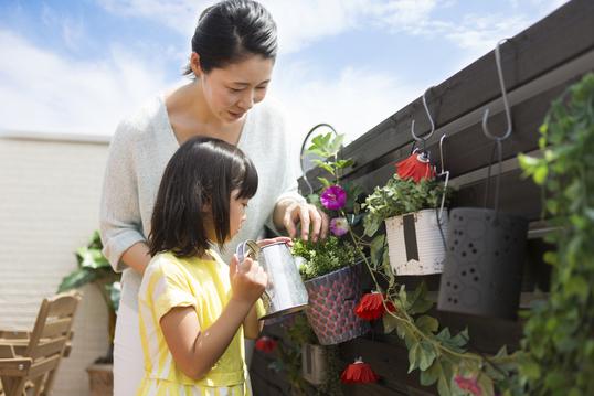 ベランダの鉢植えに水をやる親子