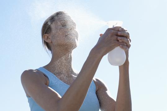 顔にスプレーを吹き付ける女性
