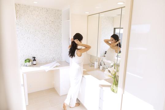 風呂上がりに髪の毛を整える女性