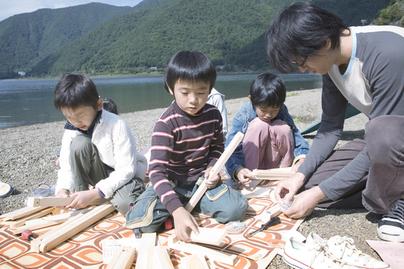 湖畔で工作をする子どもたち