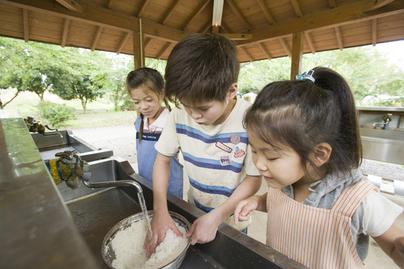お米を研ぐ男の子と見守る女の子たち